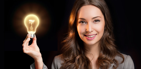 business idea: Gorgeous young businesswoman holding glowing light bulb idea symbol.