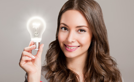 Gorgeous young businesswoman holding glowing light bulb idea symbol. 版權商用圖片 - 56326079