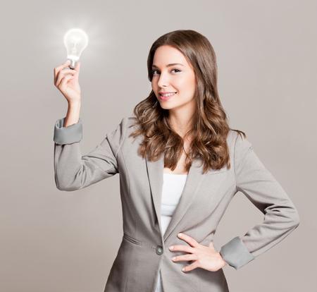 pensamiento creativo: Magnífica joven negocios la celebración de bombilla de luz incandescente idea de símbolo.