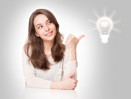 Portrait of a beautiful expressive young brunette with light bulb idea sign. 版權商用圖片 - 56466259