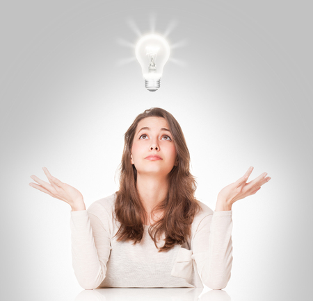 forgetful: Portrait of a gorgeous young brunette woman with light bulb idea symbol. Stock Photo