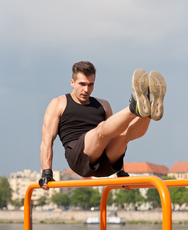 gripping bars: Strong handsome young guy doing bar street workout.