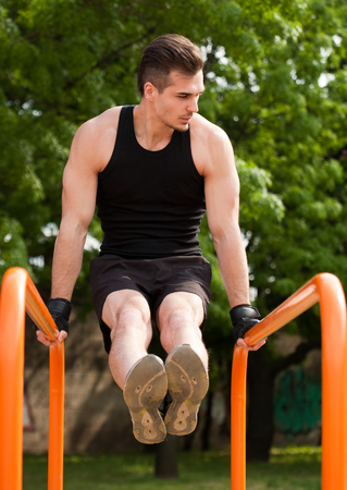 young guy: Strong handsome young guy doing bar street workout.