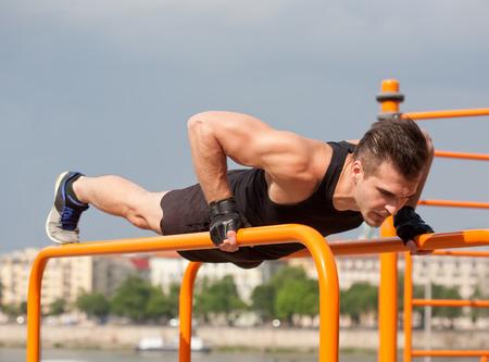 hombre fuerte: El hombre hermoso joven atleta que hace entrenamiento calle urbana. Foto de archivo