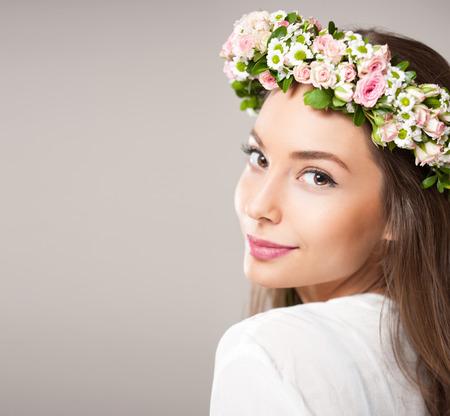 Portret van een mooie donkerbruine vrouw die lentebloem krans. Stockfoto