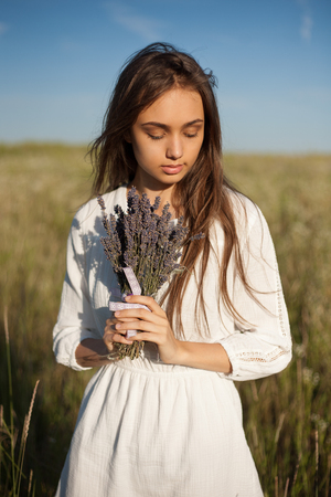 scent: Portrait of a young brunette beauty enjoying the scent of lavender outdoors.
