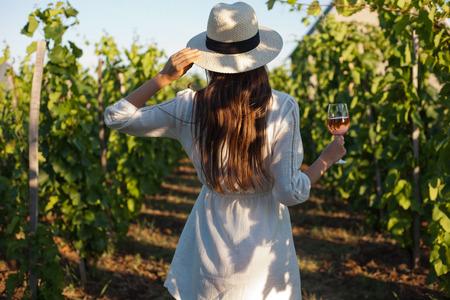 Retrato de una mujer hermosa morena se divierten vino en los viñedos. Foto de archivo