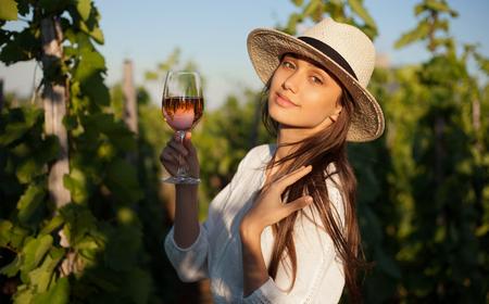 tomando vino: Portrait of young brunette beauty in the vineyards having wine. Foto de archivo