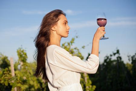 belle brune: Portrait d'une femme superbe brune ayant vin de plaisir dans les vignes. Banque d'images