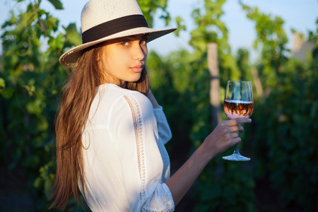 wine glass: Portrait of young brunette beauty in the vineyards having wine. Stock Photo