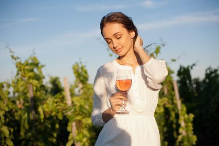 Portret van een schitterende brunette vrouw die wijn plezier in de wijngaarden.