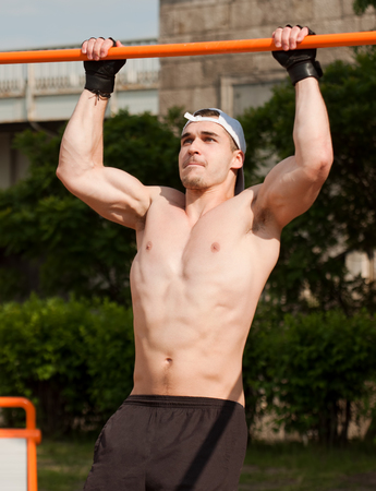 gripping bars: Handsome young athlete man doing urban street workout. Stock Photo