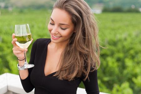 enjoyment: Outdoors portrait of a beautiful wine tasting tourist woman.
