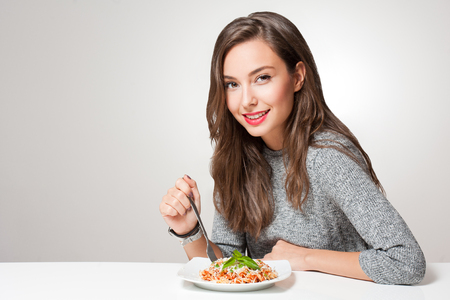 spaghetti sauce: Beautiful young brunette woman eating Italian pasta.