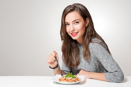 Piękna młoda kobieta jedzenie włoskie makarony.