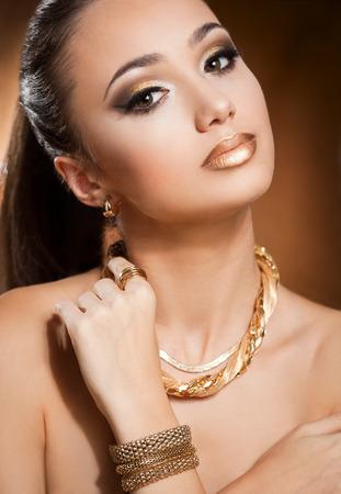 aretes: Retrato de una mujer joven y bella morena llevaba joyas de oro.