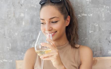 갈색 머리 아름다움 마시는 와인의 초상화입니다.
