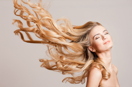 groomed: Portrait of a young blond woman with long healthy hair.