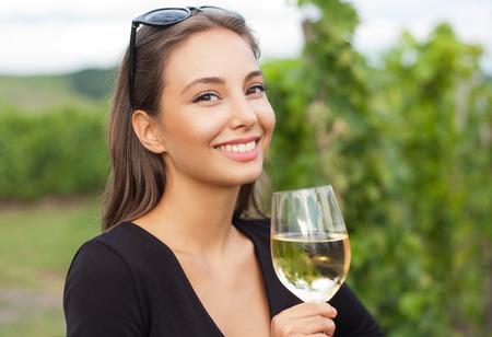 관광 여자를 시음하는 아름 다운 와인의 야외 초상화.