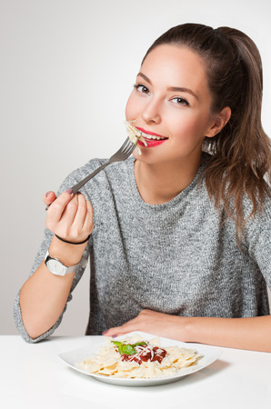 Beautiful young brunette woman eating Italian pasta. photo