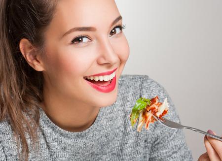 mujer joven y bella morena de comer comida italiana. Foto de archivo