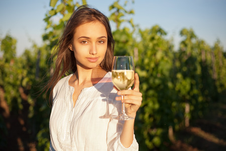 Portrait of young brunette beauty in the vineyards having wine. photo