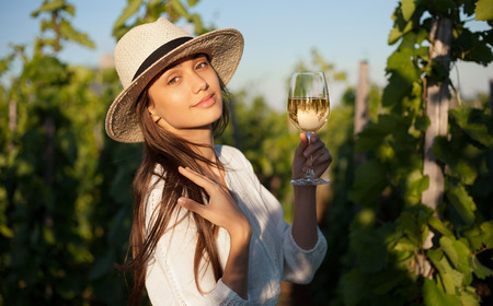 Portrait of a gorgeous brunette woman having wine fun in the vineyards. photo