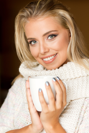 Portrait of winter fashion young blond with hot beverage.