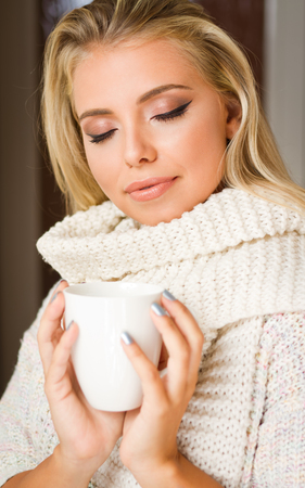 Beautiful young blond woman having cup of warm refreshment.
