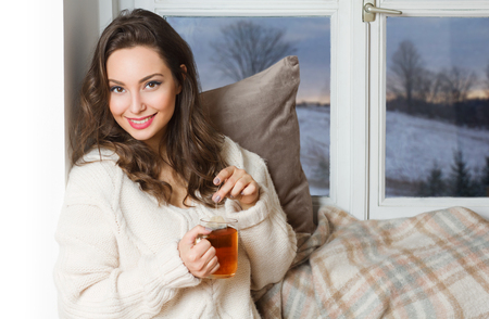 Gorgeous young brunette woman holding cup of hot beverage.