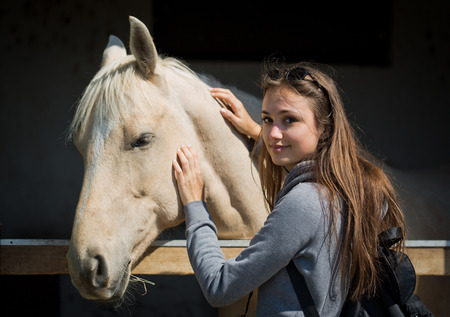 Beautiful young brunette woman befriending champagne color horse.