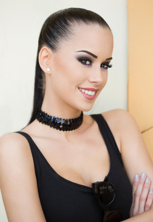 Gorgeous fashionable young brunette woman in heavy dark makeup.
