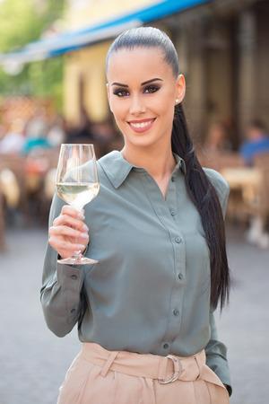 Elegant fashionable tourist woman having wine. Standard-Bild