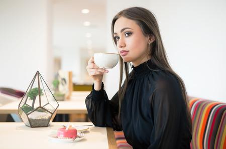 Elegant beautiful young brunette woman having coffee.