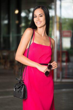 Portrait of a brunette beauty outdoors in pink summer dress. Standard-Bild