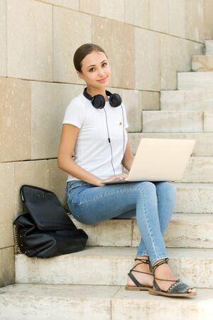 Portrait of attractive young brunette student using her laptop outdoors. Standard-Bild