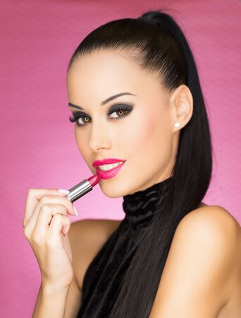 Portrait of a gorgeous young cosmetics brunette in heavy dark makeup.