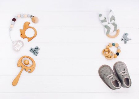 Baby accessories booties, soother and wooden toys on white wooden background with blank space for text. Top view, flat lay. Фото со стока