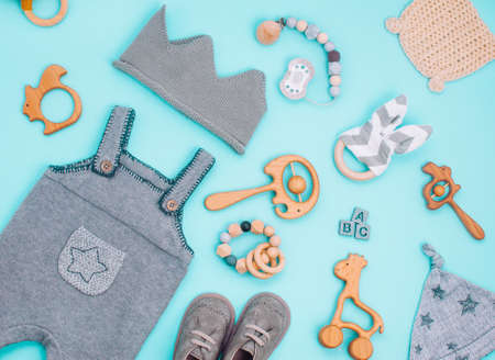 Baby clothes and wooden toys on light blue background