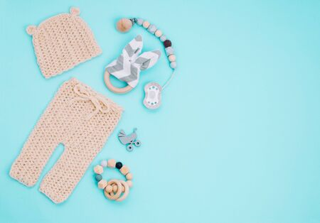Baby clothes, soother and wooden toys on light blue background with copy space
