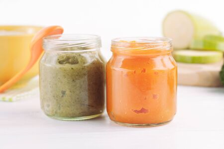 Broccoli and pumpkin vegetable puree in jars on white wooden background near ingredients