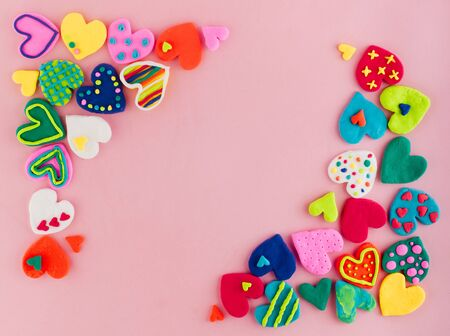 Colorful handmade plasticine hearts on pink background
