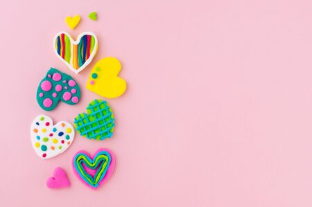 Valentines Day background. Colorful handmade plasticine hearts on pink background with blank space for text. Top view, flat lay.