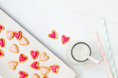 Heart shape cookies for Valentines Day and milkshake on light marble background with blank space for text. Top view, flat lay. Stock Photo