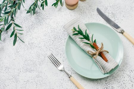 Holiday elegant table setting with linen napkin, sprig and cinnamon. Top view, flat lay. Stock Photo