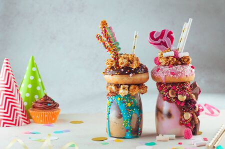 Two freak shakes topping with donut, caramel popcorn and sweets on grey background