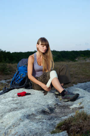 Portrait of a female tourist applying an arm medical bandage in mountains during the journey