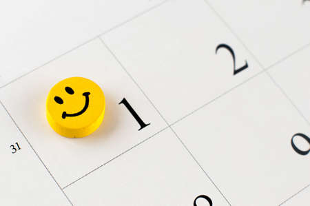 Closeup of wooden bead with drawing happy emotion on the calendar page; small depth of field. Stock Photo