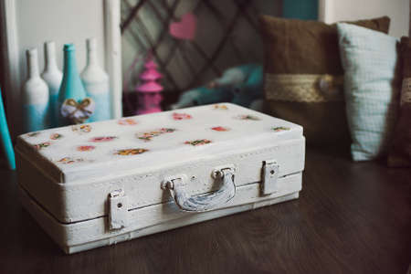 Vintage decorative white suitcase with decoupage in front of bottles and pillows on wooden floor; shot in shallow depth of field, suitcase in a focus