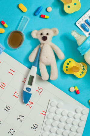Baby health care pharmacy concept: bear toy with electronic thermometer, pills, nipples and spoon of syrup on blue background top view, flat lay. Standard-Bild